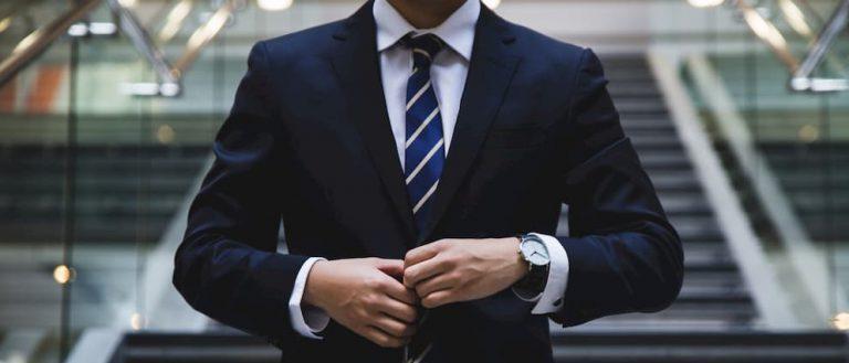 Man straightens suit jacket in outdoor setting
