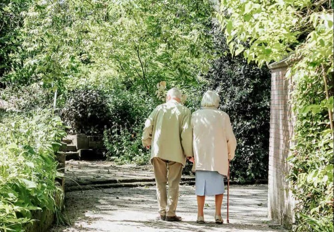 Old couple walk in a public place