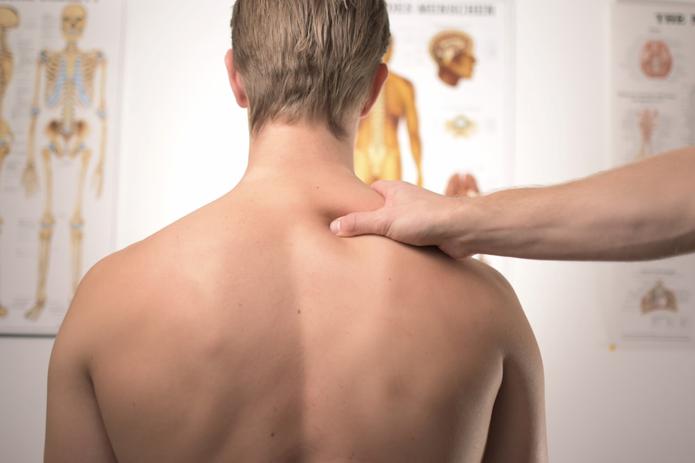 Shirtless man receives treatment on his neck for whiplash